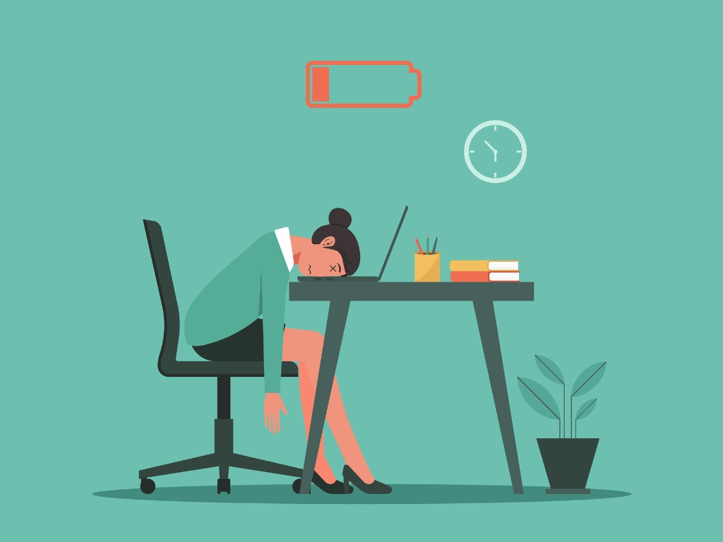How to cope with burnout: woman with head on desk, battery empty sign